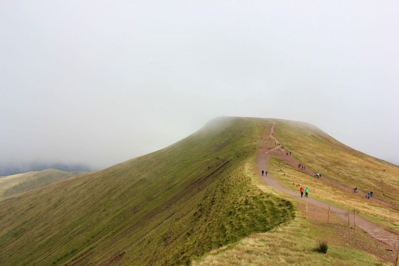 view-of-pen-y-fan-peak-from-corn-du-and-clouds-and-mountain-hikers